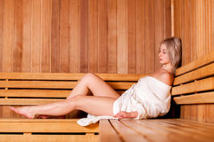 Beautiful woman sitting relaxed in a wooden sauna white coat Stock Images