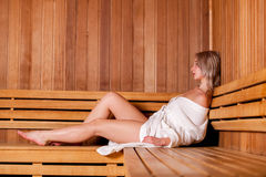 Beautiful woman sitting relaxed in a wooden sauna white coat Royalty Free Stock Photography