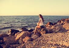 Beautiful woman sitting on the rock near the blue sea with relax Royalty Free Stock Photography