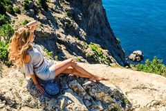 Beautiful woman sitting on a rock near blue sea. On resort Royalty Free Stock Images