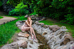 Beautiful woman sitting on rock by stream in park Stock Photo