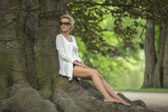 Beautiful woman sitting on the roots of a tree in the Park. Stock Image