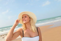 Beautiful woman sitting on a sandy beach Stock Images