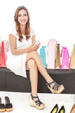 Beautiful woman sitting between shopping bags while holding mobi. Full body portrait of beautiful woman sitting between shopping bags while holding mobilephone Royalty Free Stock Photos