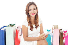 Beautiful woman sitting between shopping bags while holding mobi Royalty Free Stock Photo