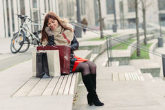 Beautiful woman sitting after shopping and talking on smart phon. E outdoor Royalty Free Stock Images
