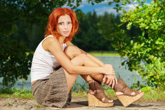 Beautiful woman sitting on shore Stock Images