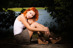 Beautiful woman sitting on shore of lake Royalty Free Stock Photo