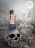 Beautiful woman sitting on the skull stock images