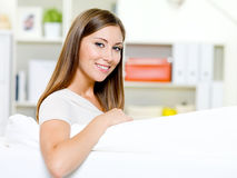 Beautiful woman sitting on the sofa Royalty Free Stock Photos