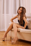 Beautiful woman sitting on sofa Stock Photography