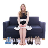 Beautiful woman sitting on sofa and choosing shoes isolated on w Stock Photos