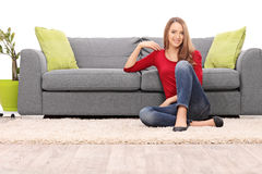 Beautiful woman sitting by a sofa on the floor Royalty Free Stock Images