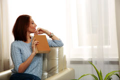 Beautiful woman sitting on the sofa and holding a book Stock Image