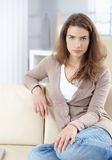 Beautiful woman sitting on sofa at home Royalty Free Stock Photos