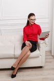 Beautiful woman sitting on a sofa. Beautiful woman in red shirt and eyeglasses sitting on a sofa Stock Images