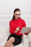 Beautiful woman sitting on a sofa. Beautiful woman in red shirt and eyeglasses sitting on a sofa Stock Photography