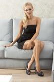 Beautiful woman sitting on sofa Stock Images