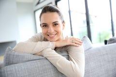 Beautiful woman sitting on sofa smiling Royalty Free Stock Photography