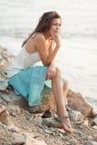 Beautiful woman sitting on stone. Beautiful brunette  woman sitting on stone near water, vertical Royalty Free Stock Photography
