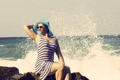 Beautiful woman sitting on a stone and splashing Royalty Free Stock Image