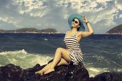 Beautiful woman sitting on a stone and splashing Stock Image