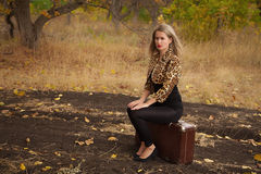 Beautiful woman sitting on a suitcase. In autumn Royalty Free Stock Photos