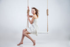 Beautiful  woman sitting on swing  isolated Stock Photo