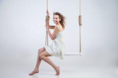 Beautiful  woman sitting on swing  isolated Stock Photo