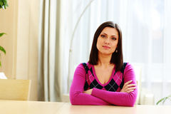 Beautiful woman sitting at the table with arms folded Stock Photo