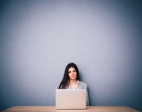 Beautiful woman sitting on the table with laptop Royalty Free Stock Photos