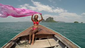 Beautiful woman sitting on thailand boat nose action camera pov, raising pink pareo young girl happy smiling stock footage