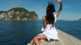 Beautiful woman sitting on Thailand boat nose in sea back rear view action camera pov, young girl in white stock video