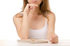 Beautiful woman sitting thinking pen notebook Stock Images
