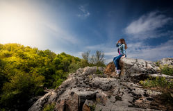 Beautiful woman sitting on top of cliff and looking at sunset Royalty Free Stock Images