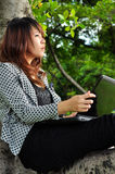 Beautiful woman sitting on the tree and playing laptop Royalty Free Stock Photo