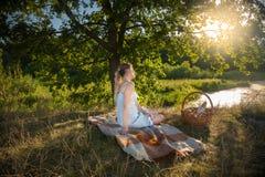 Beautiful woman sitting under big tree at field and looking at s. Beautiful young woman sitting under big tree at field and looking at sunset Stock Photo