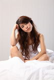 Beautiful woman sitting up in bed looking tired Royalty Free Stock Image