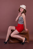 Beautiful woman sitting on a vintage suitcase. Studio shot Royalty Free Stock Images