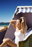 Beautiful woman sitting on a wicker chair enjoying the sun on th. Beautiful woman moving the hair up sitting on a wicker chair enjoying the sun on the beach Stock Image