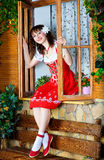 Beautiful woman sitting on the window sill Royalty Free Stock Image