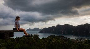 Beautiful woman sitting on wooden platform with Phi Phi island views and cloudy sky stock images