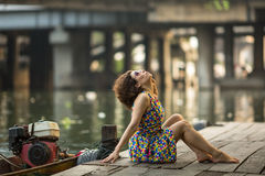 Beautiful  woman sitting on a wooden river pier. Royalty Free Stock Photography