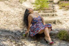 Beautiful woman sitting on a wooden stairs in the middle of an arid terrain. With her head back with a long black hair in a blue dress with flowers, enjoying a stock photography