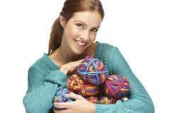 Beautiful woman sitting with yarn rolls, smiling Stock Photos