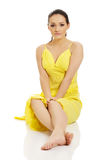 Beautiful woman sitting in yellow dress. Royalty Free Stock Image