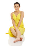 Beautiful woman sitting in yellow dress. Royalty Free Stock Photography