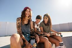 Beautiful woman at skate park with friends. Beautiful women sitting on ramp with friends at skate park. Cheerful girls relaxing at skate park Royalty Free Stock Photo