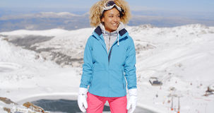 Beautiful woman in ski outfit standing on mountain Stock Photo