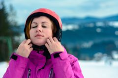 A beautiful woman skier wears a helmet and fixes it for safety stock images